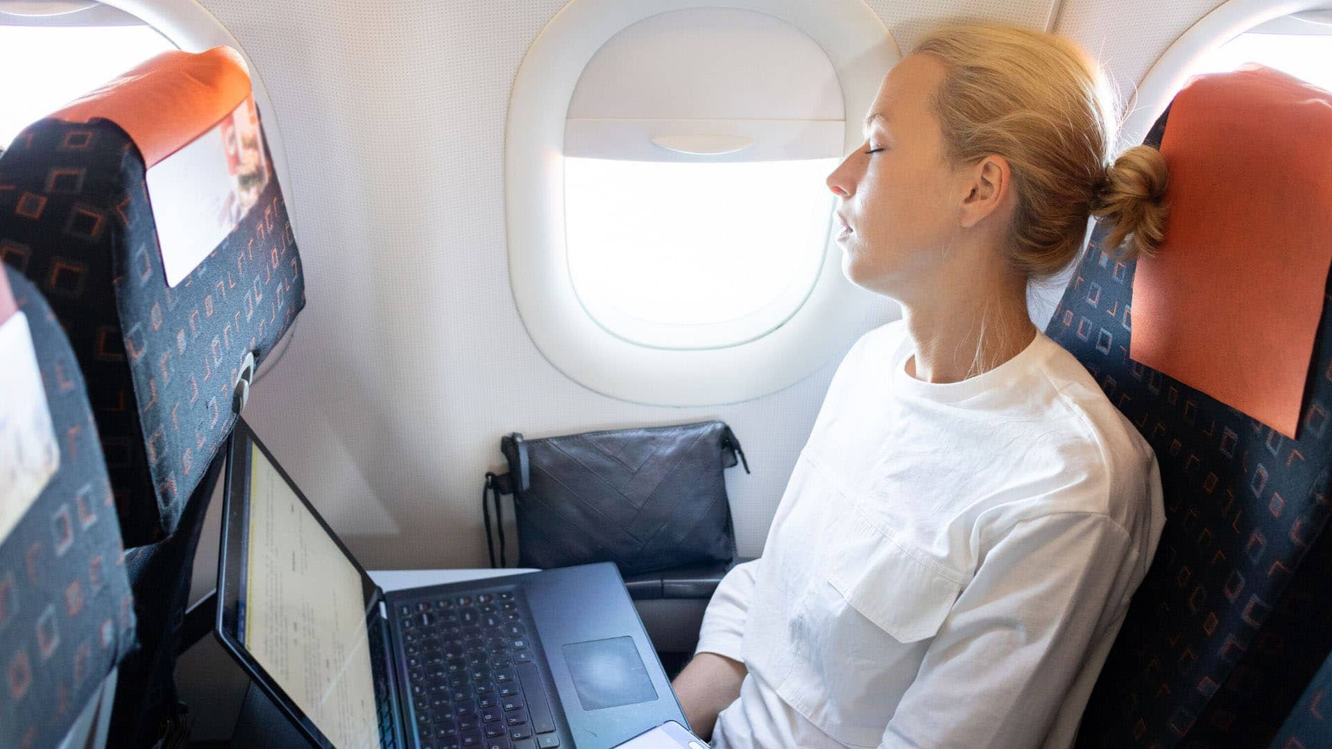 Blonde woman with bun asleep on airplane with laptop