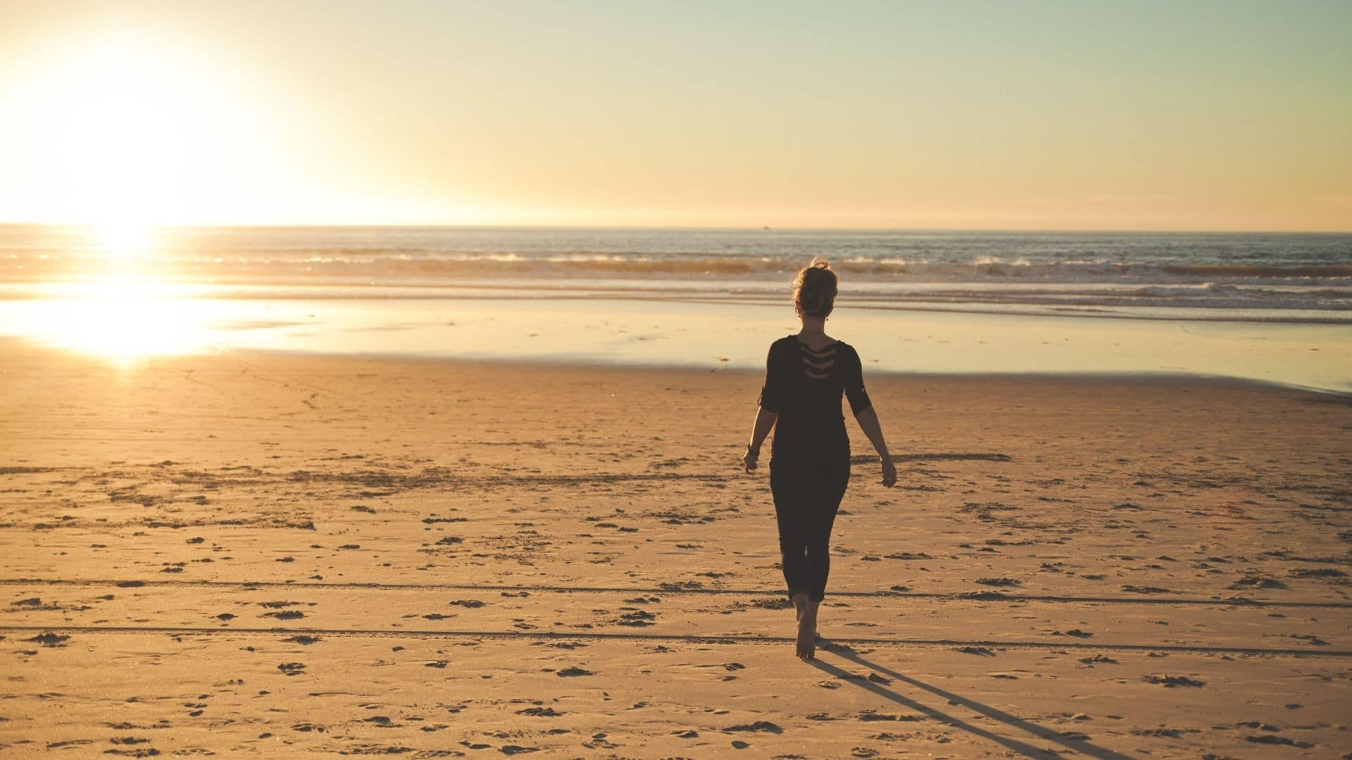 woman walking at sunrise on beach