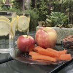 a table with apple, lemon water, almonds, and carrots