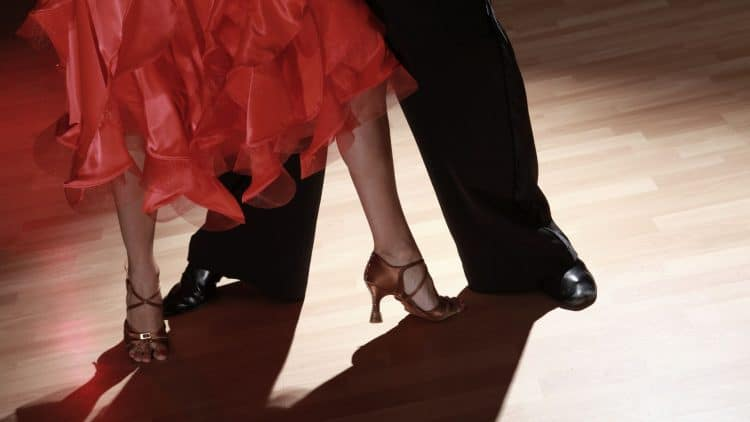 feet of two people dancing in a red dress