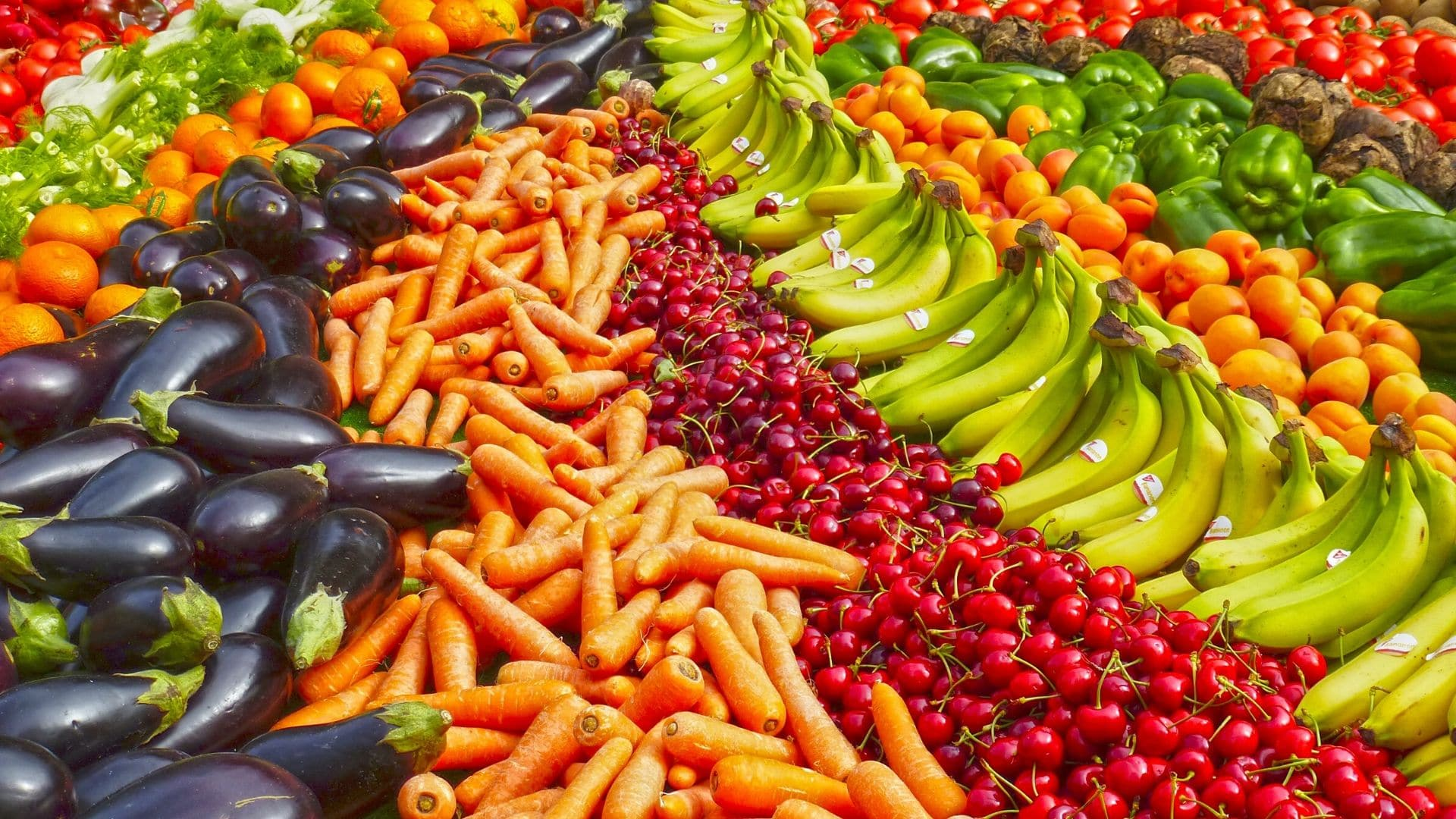 a bounty of fruit and vegetables shaped in a rainbow