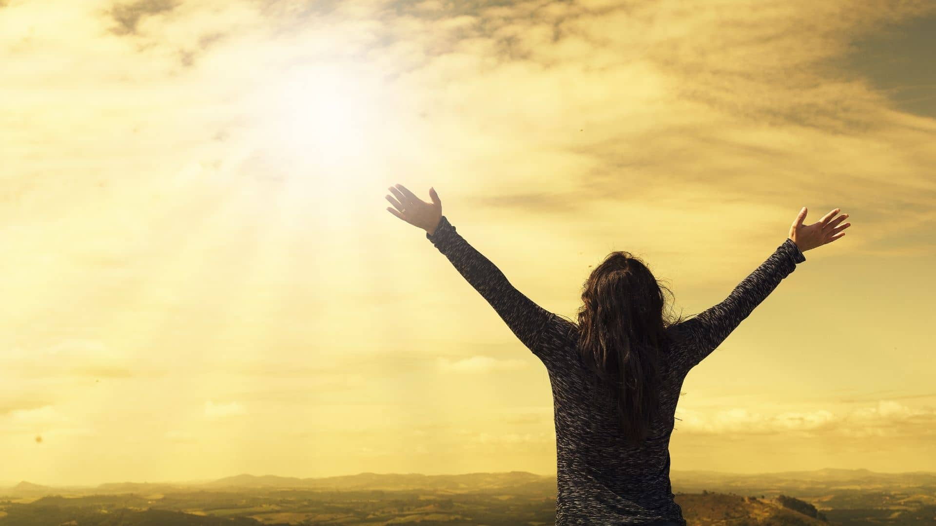 Woman throwing her arms up in hope to the sun to celebrate being cancer=free