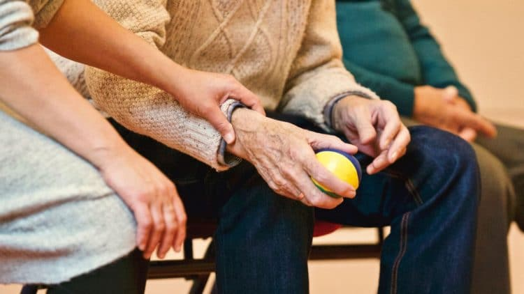 alzheimer's hand being touched by a caregiver