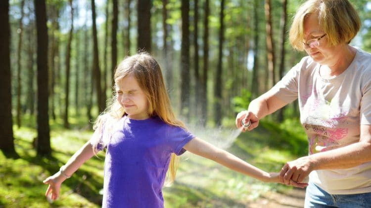 woman spraying a child in a purple tshirt with bug spray when in the woods