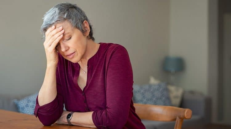 short-haired middle aged woman with burgundy top puts hand to head due to stress