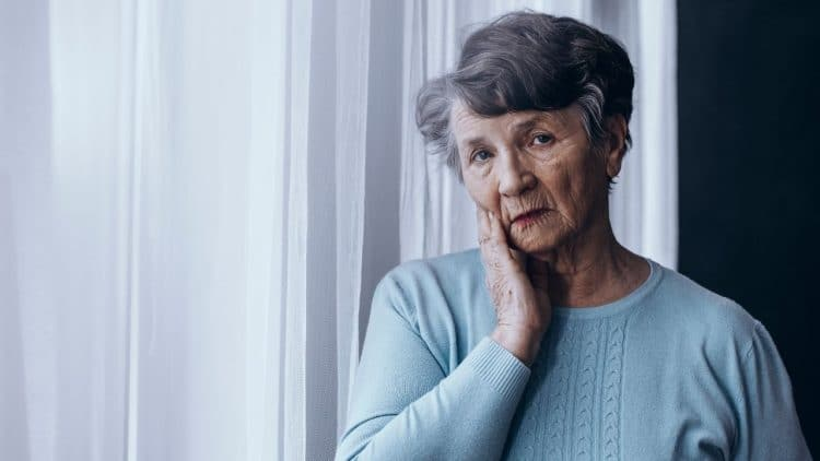 woman standing near window with hand on face with a blue sweater with alzheimer memory issue