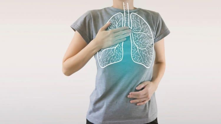 women hand on chest over a superimposed image of a lung on a grey tshirt