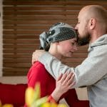 woman with scarf on head getting kissed on forehead. she has cancer
