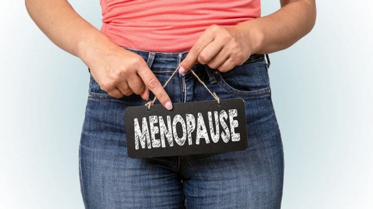 woman in jeans holding a menopause sign
