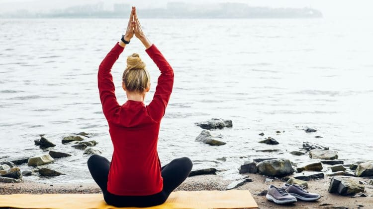 woman sitting crossed legged in front of ocean on a yoga mat