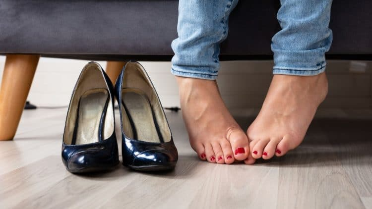 woman sitting on couch with shoes off