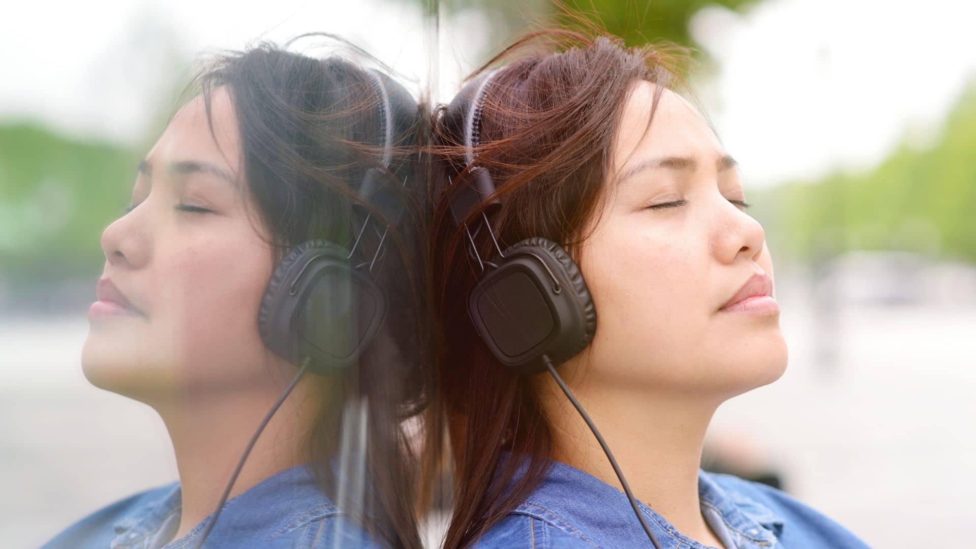 asian woman leaning against a glass building with headphones closed eyes