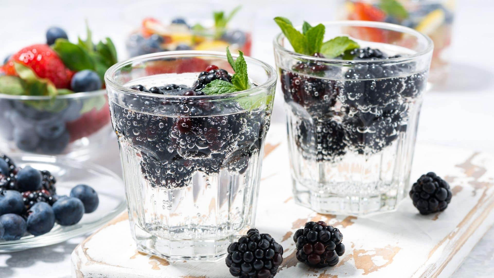 two glasses of carbonated water with blackberries.