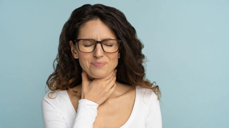 woman with glasses holds her throat in pain
