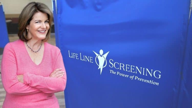 Nurse Barb in a pink sweater next to a Life Line Screening Divider in blue