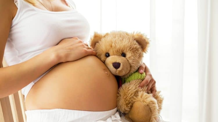 pregnant woman holding a teddy bear to her belly as she sits