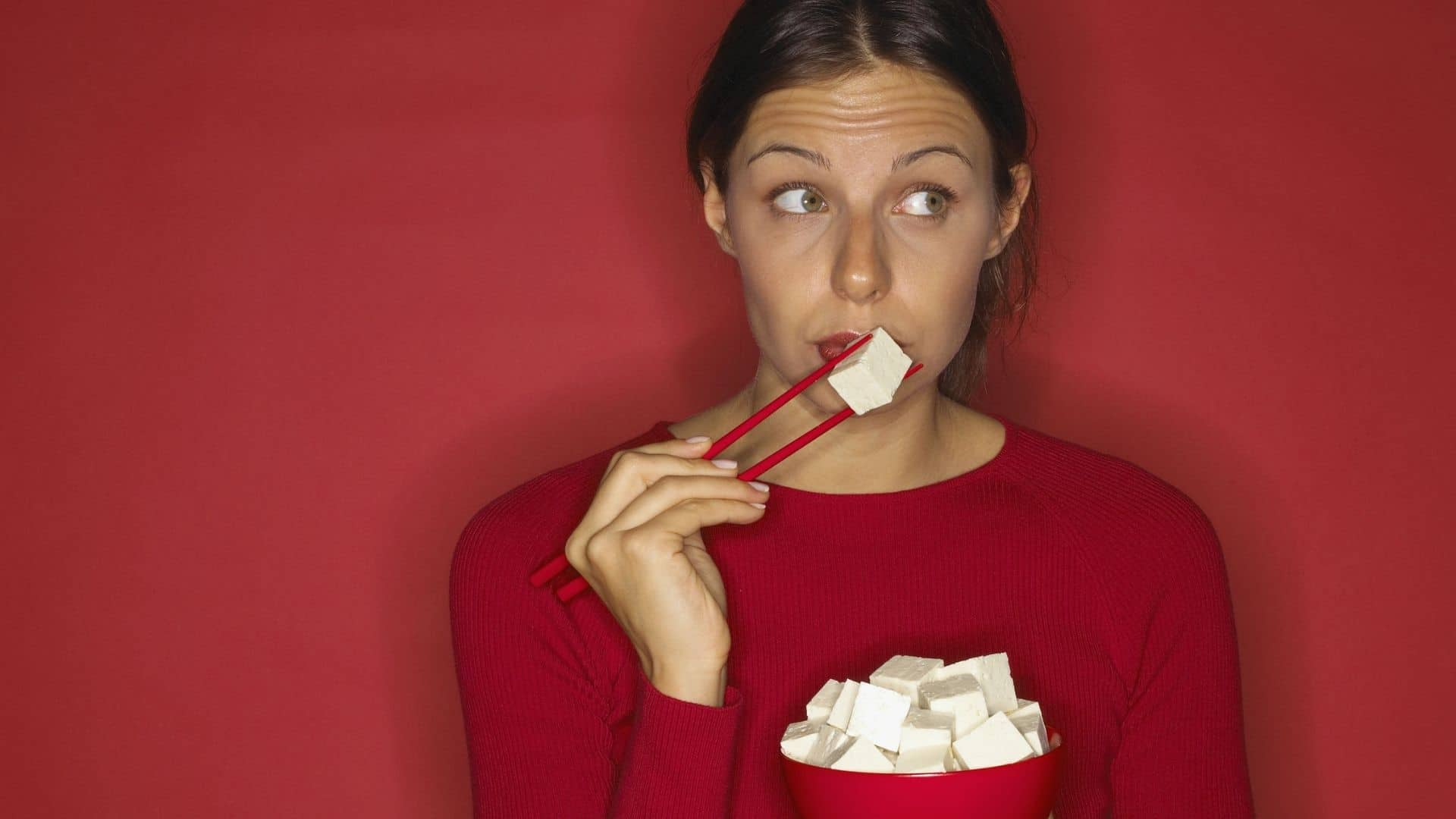 green-eyed woman in red top against a red background eats a bowl of tofu with chopsticks